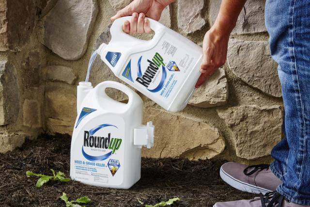 RoundUp weed and grass killer refill pouring into sprayer